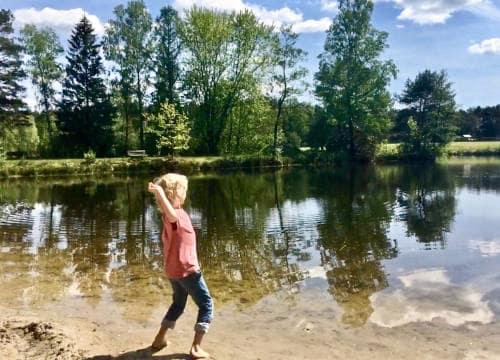 Kleiner Junge wirft einen Stein in den Badesee vom Reiterhof Severloh