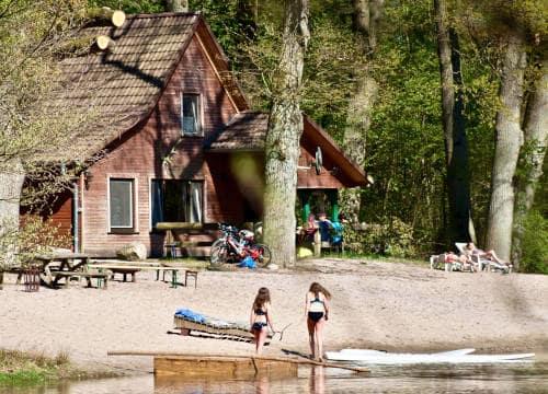 Blick auf das Ferienhaus Jagdhaus über den Badesee auf den Strand vom Reiterhof Severloh