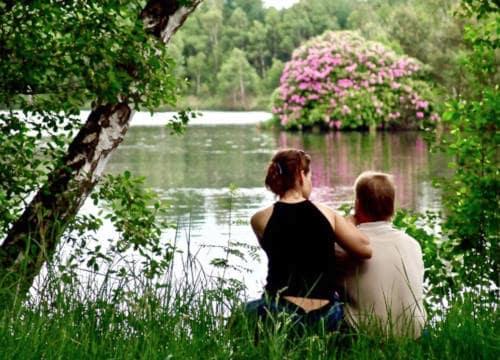 Ein Paar sitzt romatisch am Badesee und schaut auf den Rododendronbusch auf dem Reiterhof Severloh