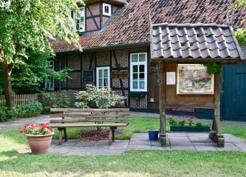 Informationstafel dea Reiterhof Severloh mit Bank vor dem Haupthaus zum Biergarten