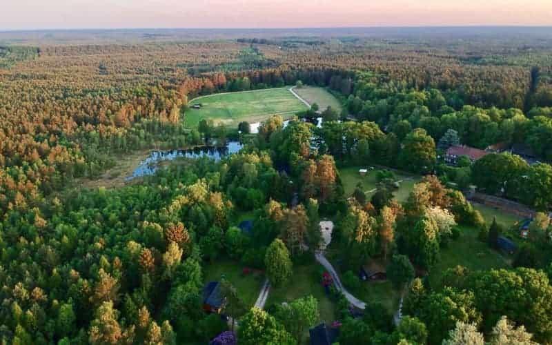 Luftbild mit Blick auf die Unterkünfte, Wald, Wasser und Weiden vom Ferienhof und Reiterhof Severloh