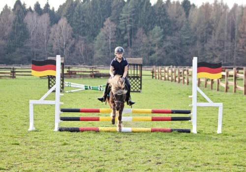 Kind springt mit Pony über ein Hindernis auf dem Springlatz vom Reiterhof Severloh